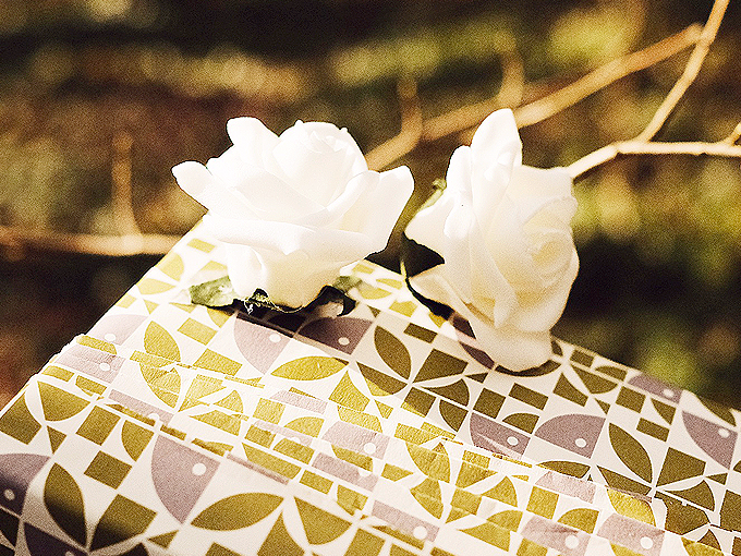 Personally wrapped gift in premium white, gold, silver and paper with white roses